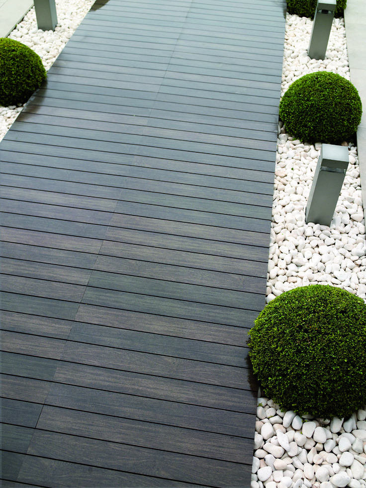 Wooden decking pathway bordered by pale gravel/decorative chipping topiary balls and post lighting