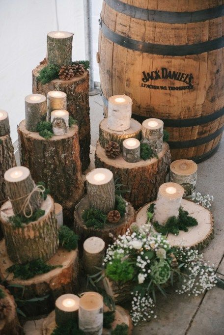 We love this DIY-friendly wedding decor made up of cuts of wood topped with candles and sprinkled with wild greenery, moss and pine cones. Taylor and Joshua's Woodland Deer-Themed Wedding via Love Inc.   photo by Allie Siarto Photography #rusticwedding #diywedding #barnwedding