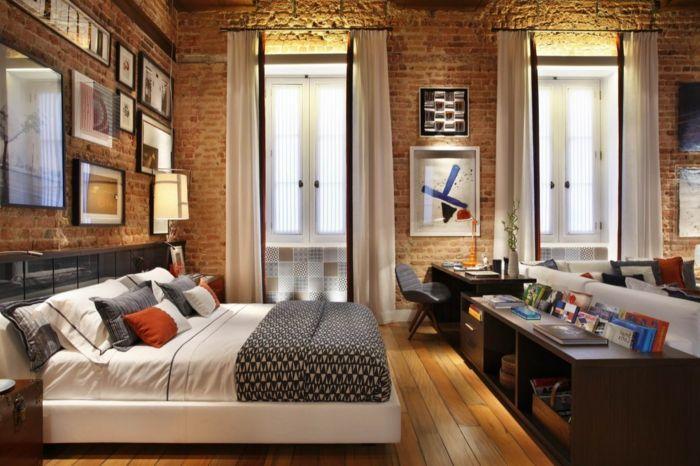 paneles decorativos, dormitorio con cama doble y escritorio, paredes de ladrillo con cuadros, ventanas grandes con cortinas blancas