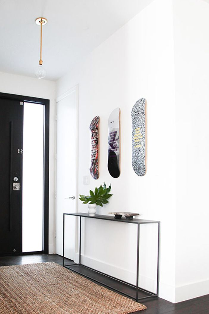 Skateboards above thin console table + minimal styling + bare bulb light fixture + black door