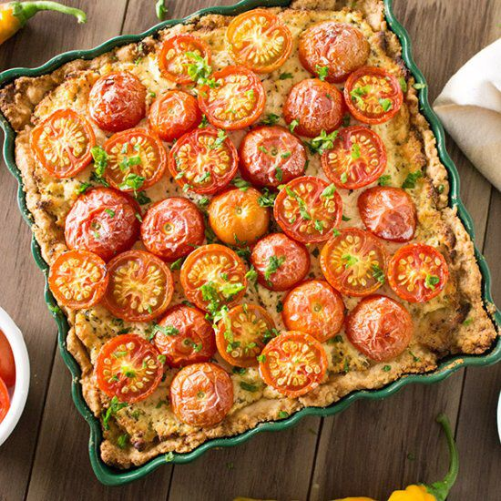 A cheese tart recipe made with ricotta and Parmesan cheeses and garden fresh globe tomatoes, served with pesto.