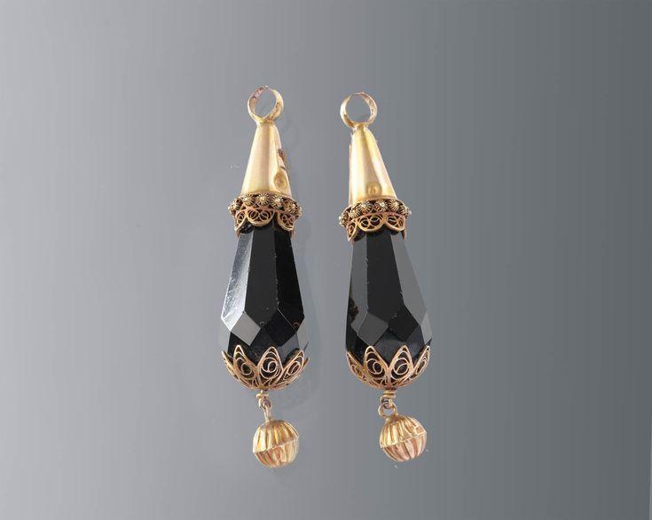 Paar 'rouwklokken'. Gedragen door een vrouw te Axel bij de rouwdracht, omstreeks 1880-1900. De rouwklokken werden aan de gouden 'krullen' (oorijzeruiteinden) gehangen. #Axel