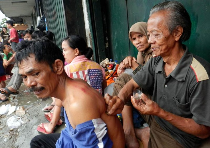 A man gets a coining massage at a shelter after being evacuated from his flooded home overnight in Jakarta on Friday, January 18, 2013 | © Bay Ismoyo | AFP Photo