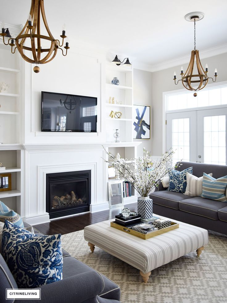 Painting walls white and accessorize grays, blues and cream to get the same look for your living room.