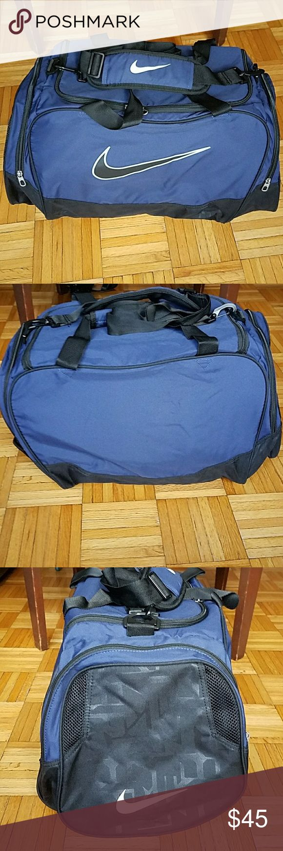 """Nike Duffel Bag -Spacious & Lightweight Blue Nike Duffel Bag -used once! Now just sitting in the closet - like new condition! -can be hand-held (two handles-photo #6) but also has an adjustable shoulder strap with Nike logo -one main u-shaped opening compartment with inside zelcro pocket, 2 side compartments on outside of bag -approximately 18"""" length not including side compartments, 11"""" height -has an area inside the handles where you can write your name -100% polyester Nike Bags"""