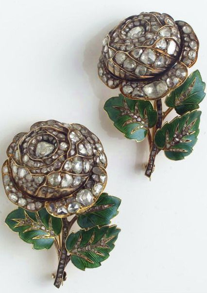 A pair of diamond, enamel and gold brooches the matched brooches of rose motif, the 14k gold flower tops set throughout with rose and table-cut diamonds, completed by a 14k gold stem with 18k gold leaves, decorated with green enamel, accented by table-cut diamonds. (minor loss to enamel)