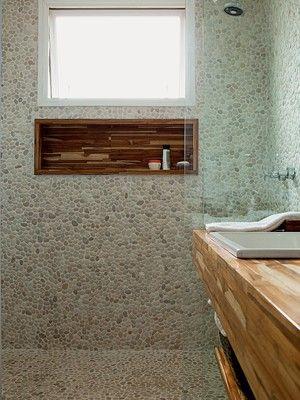 Natureza no banheiro: revestimento de seixos telados na cor areia em placa, 30 x 30 cm, R$ 250 o m², da Palimanan (evitam escorregões na área molhada). Fora dela, o piso é de porcelanato Loft SGR, da Portinari. Abaixo da janela, a arquiteta criou o nicho com madeira teca, da Interbagno, que também está na bancada com uma prateleira embaixo. As duas cubas de sobrepor (L870) e a ducha (1990CCT) são da Deca. Torneiras Triplus, da Docol. Espelho com moldura da FastFrame. Toalheiro da Ketesi.)