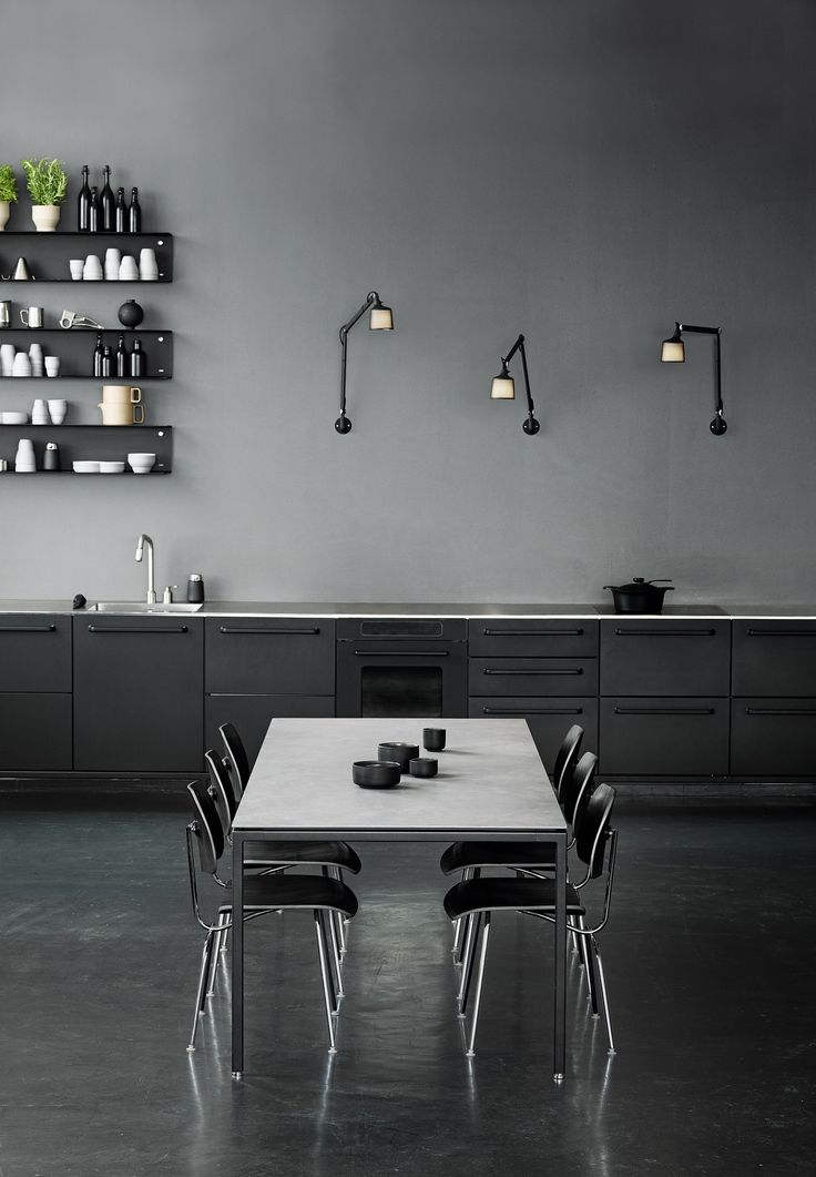 A stunning black kitchen, with open shelving instead of units. A polished concrete floor and Vipp's minimal dining table complete the monochrome look