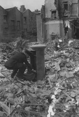 Old Kent Road, London, September 1940. Business as usual for a postman collecting mail from a battered pillar box.