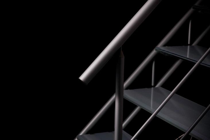 「最小限の部材による構成」というTASのコンセプトは、アルミ室内階段としての美しさを追い求めていく過程で生まれました。ガラスの透明感によって空間に明るさを実現すると同時に、照明効果によってさらに豊かな表情を生み出します。 また、アルミフレームから反射する柔らかい光は、ガラスの硬質感をさらに際立たせます。室内階段として必要な機能を満たすだけでなく、インテリアに適度な緊張感を生み出します。これ以上そぎ落とせないところまでスリムになったストラクチャーと、飾り気のない素材自身が持つ純粋な美しさこそ、私たちが本来求めていた形状美だと考えます。