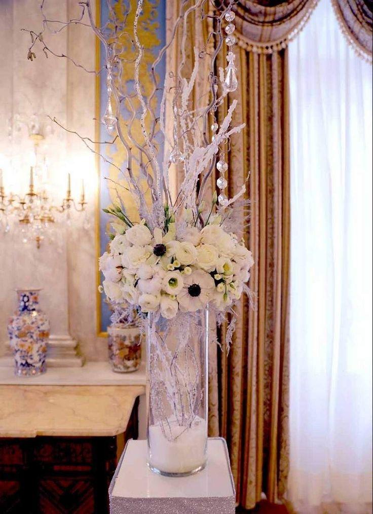 déco mariage hiver - vase haut et transparent avec un arrangement d'anémones et roses blanches, branches givrées et pampilles