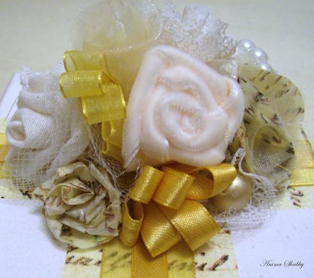 Scatola regalo con composizione di fiori di carta, tessuto e perline