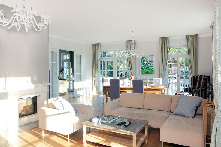 Francouzská okna přivádějí do obývacího pokoje sjídelnou dostatek světla. Zároveň umožňují rychlý přístup na terasu azahradu. Celá místnost působí útulně idíky krbu azávěsům vanglickém stylu. FOTO ROBERT ŽAKOVIČ