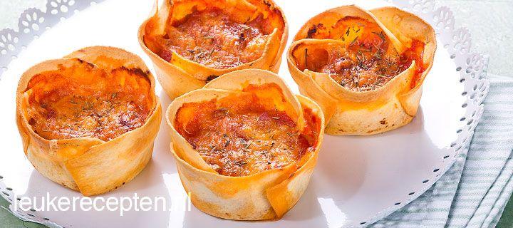 Mini lasagne HAPJE – 30 MIN + 25 OVENTIJD – 12 STUKS **  Een leuk idee voor op een feestje; mini lasagne uit een muffinvorm   Ingrediënten 100 gr gehakt 1 eetl olie 75 gr geraspte kaas 400 gr tomatensaus ½ courgette  1 teentje knoflook  Peper en zout  1 theel suiker 12 verse lasagnebladen  Boter om in te vetten Tijm of oregano
