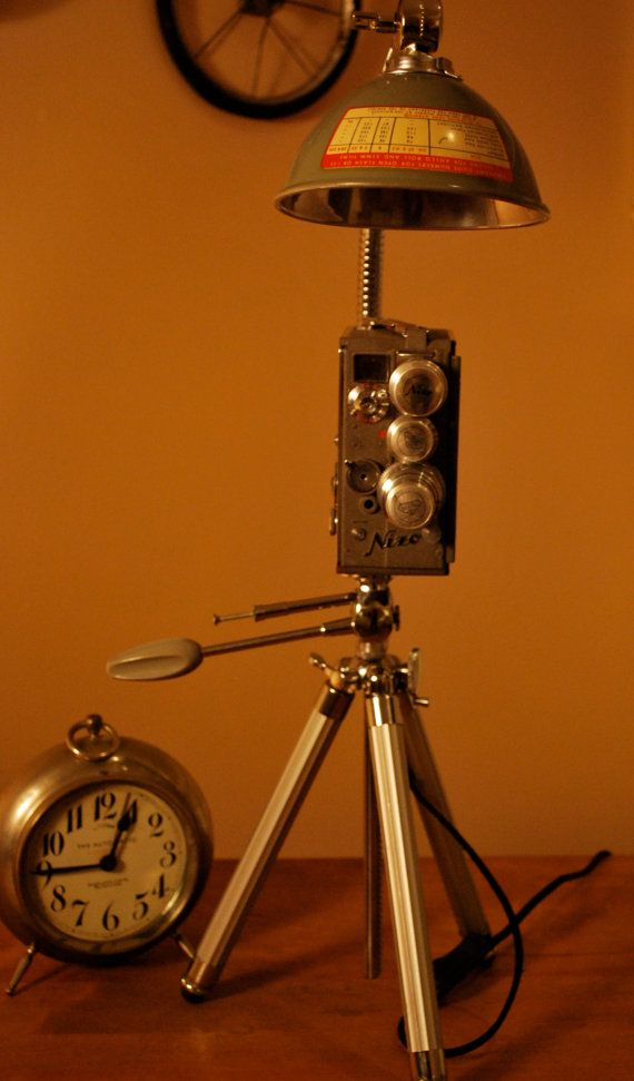 These Very cool Task light is made from up-cycled VIntage Cameras and Vintage Tripods from the 1950s and 60s.. The Camera used on this light is a Mint 1951 NAZO Heliomatic 8mm movie camera with a 3 lens. The Vivo tripod is from the 60s.. The shade is a Flash reflector from a ANSCO TLR camera. Both camera and shade are gray in color.. The light is a 1w LED light in a magnified aluminum housing and vintage (new) Rayon wrapped cord with on/off switch. The lamp stands 22 inches. This light ...