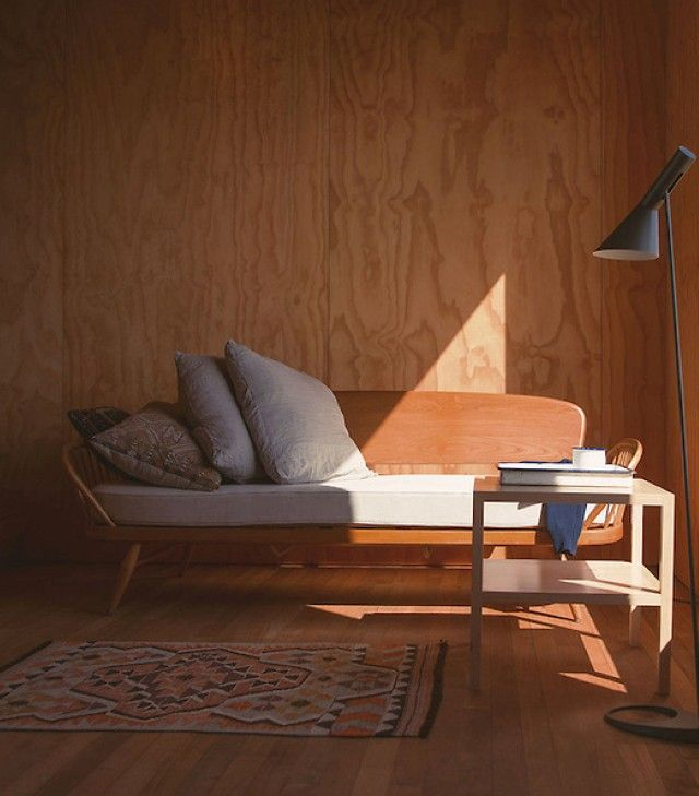 Ercol Setee | Wood wall + bench with comfy pillows + black floor lamp