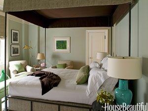 """Modern Traditional Green Bedroom Canopy beds are a favorite of designer Timothy Whealon, """"as long as they're not too dressed. I like air and space. This is a cozy, clean, modern bedroom with classical lines."""" For this New York apartment's bedroom he chose Farrow & Ball's Parma Gray on the walls because it plays up the greens of the pillows and bench of the turquoise of the 1960s lamps."""