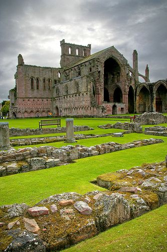 Melrose Abbey is a Gothic-style abbey in Melrose, Scotland. It was founded in 1136 by Cistercian monks on the request of King David I of Scotland.  The last abbot was James Stewart, natural son of James V, who died in 1559.Scottish kings and nobles are buried at the abbey. The embalmed heart of Robert the Bruce is also said to rest on the abbey's grounds, while the rest of his body is buried in Dunfermline Abbey.