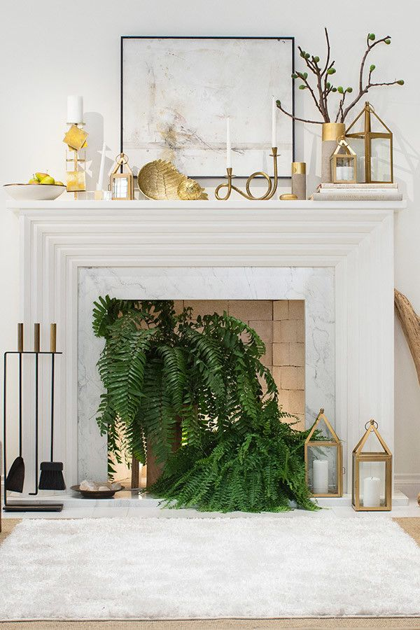 Bringing plants—like these two Boston ferns—are a cheap and easy way to break up the lines of the mantel and fill an inactive space.