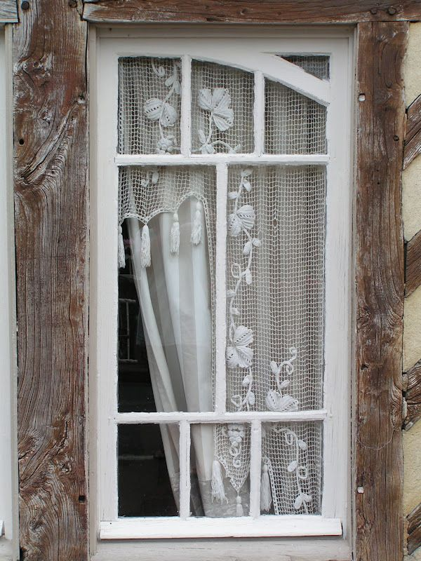 Antique panes framed with cottony white guipure.