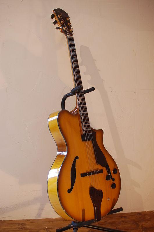 """このギターのコンセプトは、""""JAZZ""""と""""ACOUSTIC""""の中間を目指したモデルです。 一見、フロント・ピックアップ一発のいわゆるJAZZギター、に見えますが、ピエゾ・ピックアップも内蔵されており、フロント・ピックアップにミックスさせる事で様々な音作りが可能です。 表板、裏板もフォークギターに近い厚みまで削られており、生鳴りもフォークギターに近づけています。 張る弦ですが、実は何でも合うんです。ダキストのフラット・ワウンドを張ればジャズ寄り、ラウンド・ワウンドの太めを張ればフォーク寄り、現在は中間をとって、明るめのサウンドが特徴のダダリオのフラット・ワウンドを張っています。"""