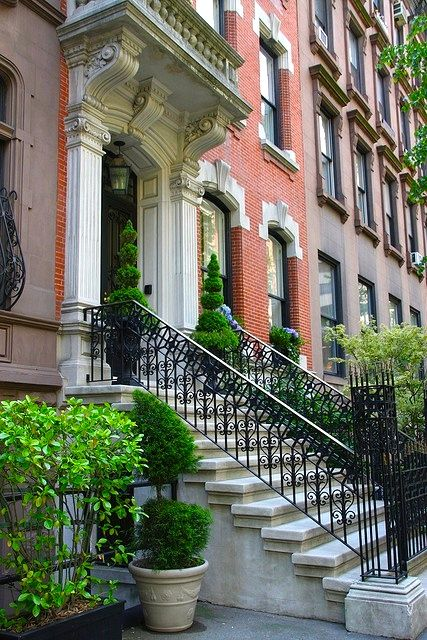 Look closely at this slice of perfection:  Besides the fabulous stonework and equally amazing ironwork, look at those steps, the potted greenery...and there are blue hydrangeas in the window boxes!