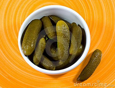A closeup up pickled cucumbers in a small   bowl on  plate