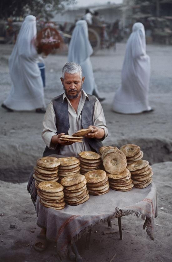 Amazing is the women in the background!  Bread vendor, Afghanistan | Steve McCurry