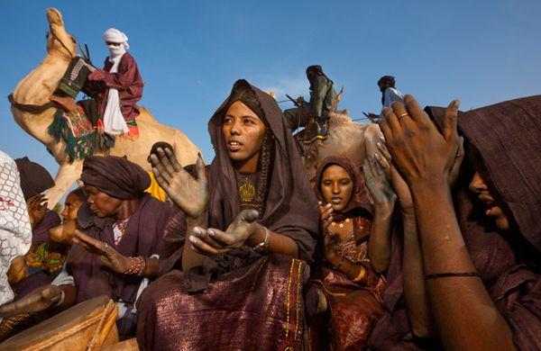 Con le mani macchiate dalla tintura indaco degli abiti nuovi, un gruppo di donne tuareg festeggia una nascita. Tra i Tuareg, per tradizione, le donne non si coprono quasi mai il volto: di solito sono gli uomini a celarsi dietro un turbante che lascia scoperti soltanto gli occhi.