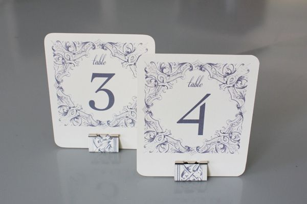 Make these DIY Table Numbers and coordinating holder from re-purposed binder clips. Project includes free printable table number templates.