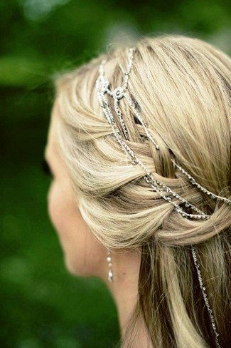 A long braided half-up half-down waterfall bridal hairstyle with glittery hair jewellery snaking between the braids.