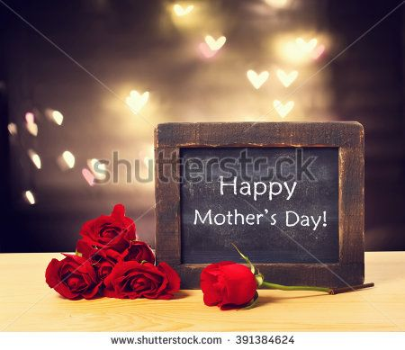 Happy Mothers day message on a small chalkboard with red roses