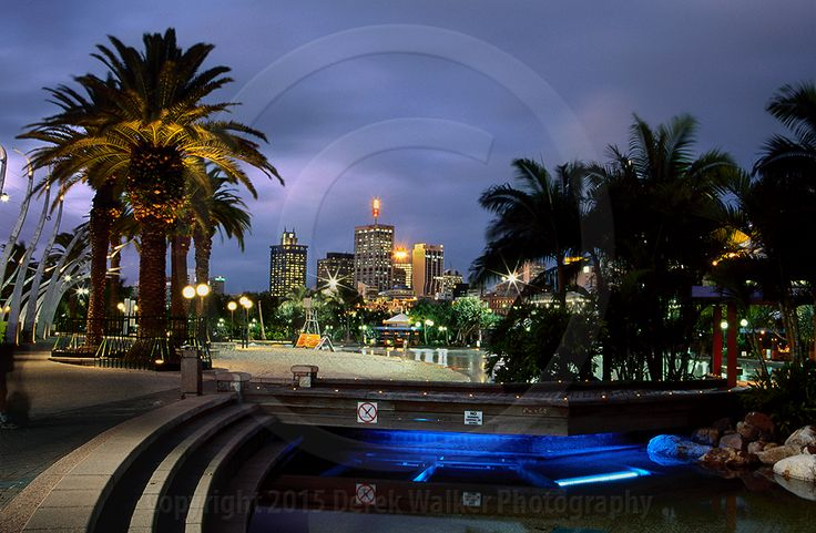 The South Bank Parklands and lagoon at twilight, with the Brisbane CBD in the…