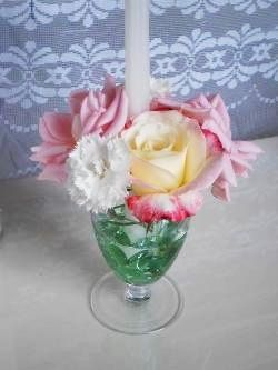 taper candle and flower arrangement in wineglass