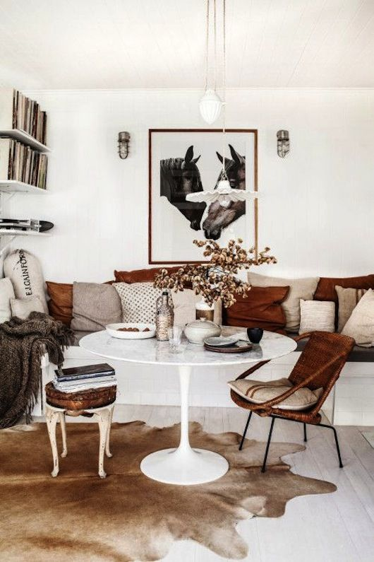 Love the simple white round table on a cow hide.... the layering of tone on tone, browns, whites, greys, makes for a very scrummy look!