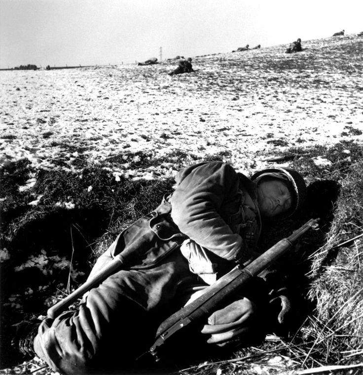 A U.S. Army soldier rests in his foxhole in freezing temperatures during the Siege of Bastogne. The Siege of Bastogne was an engagement in December 1944 between American and German forces at the Belgian town of Bastogne, as part of the larger Battle of the Bulge. The goal of the German offensive was to reach the harbor at Antwerp. In order to reach it before the Allies could regroup and bring their superior air power to bear, German mechanized forces had to seize the roadways through eastern…