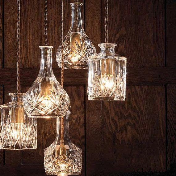 Lindas luminárias feitas a partir de garrafas de licor. A mistura de vidro liso e jateado fica muito elegante.  Fotografia: Pinterest.