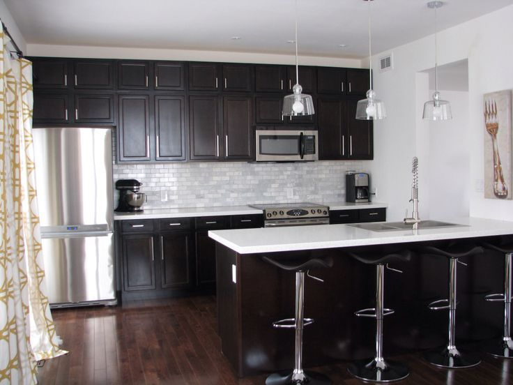 Kitchen With Dark Cabinets And White Quartz Counters, White Subway Tiles  And Pendant Lighting Over Peninsula.