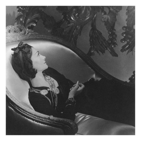 "Gabrielle ""Coco"" Chanel, 1937. The designer reclines in profile on a chaise longue, holding a cigarette. She wears a simple dark dress—an example of the ones that catapulted her to fame—and gold medallion necklaces, another trademark of the designer, who was credited with inventing costume jewelry. A simple ribbon in her hair, Chanel exudes the elegant simplicity that characterizes her brand to this day. Photo by Horst P. Horst."
