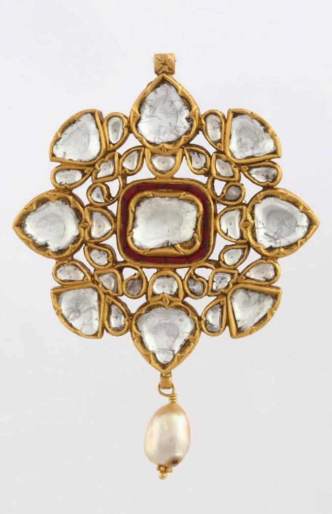 A 'POLKI' DIAMOND PENDANT Of openwork design, kundan-set with large table-cut 'polki' diamonds and rubies, and suspending a single pearl tassel