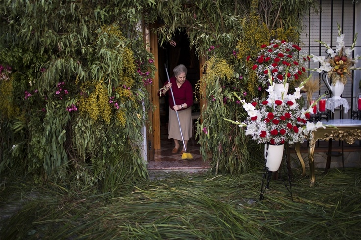 Emilio Morenatti / APA woman cleans the floor of her house decorated with flowers and branches as she waits for a Corpus Christi procession in Zahara de la Sierra on June 2, 2013.