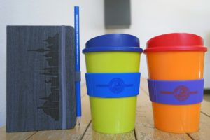 New products at the FAU shop: a stylish notebook with the skyline of Erlangen and Nuremberg and the coffee mug Americano in two different colours. (Image: FAU/Celina Henning)