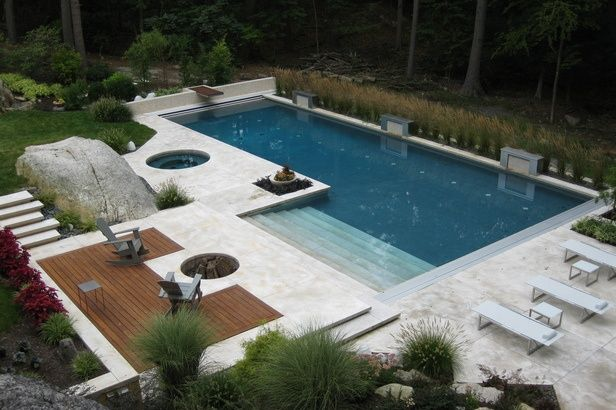 Everything about this pool and deck is absolutely perfect! Built in firepit. Lovely plant palette. White Marble. Exposed rock outcropping. Forest in the back ground. Its an absolute dream space!