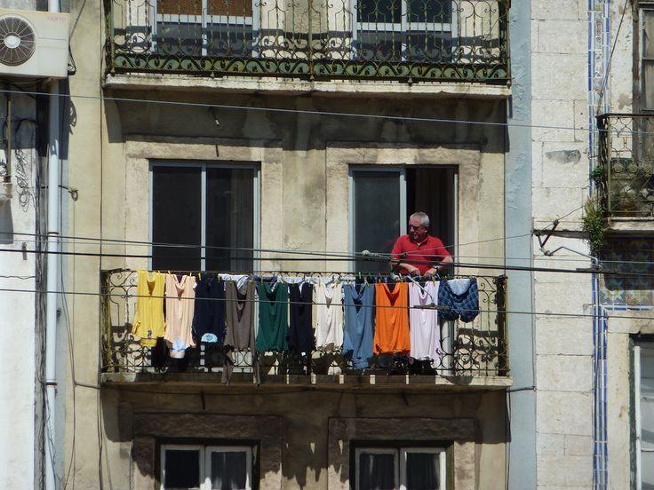 man hanging laundry lisbon