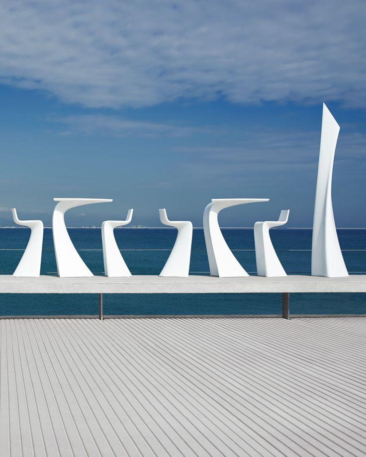 Le Mobilier Wing en forme de queue de baleine répond magnifiquement au bleu du ciel sur cette terrasse en plein air et bord de plage. Inspiration pour une terrasse de restaurant, bar, Lounge… #bleu #inspiration #professionnel #mobilier #table #tabouret  #outdoor #bar#restaurant  #barazzi