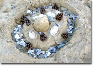 A small world built in the sand from seashells, rocks & pine cones