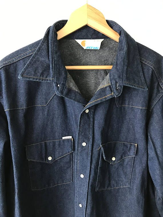 Super clean vintage Carhartt Denim shirt/ jacket (sort of like a shirt/light jacket hybrid - super thick material). Via late 80s. Features pearl colored snap buttons. Very clean and well kept. Looks hardly worn. Awesome staple piece. Fits very big so please read measurements!  Size 19x36