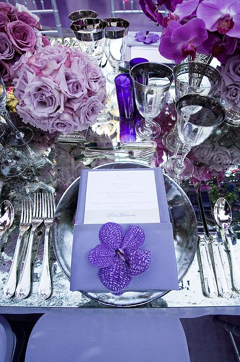 Layer shades of the same bold hue to add depth when setting a wedding table.Here, violet linens work well with mauve roses and indigo votive-holders.