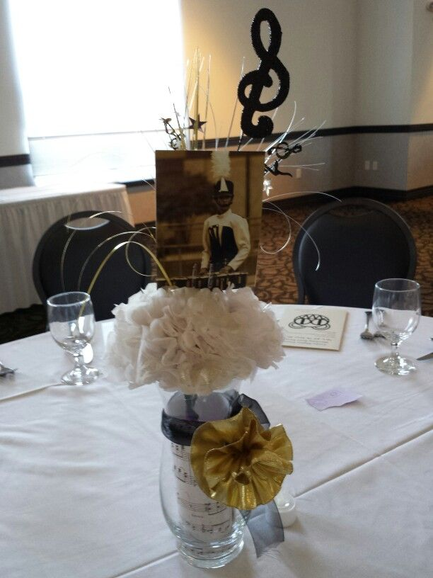 Marching band banquet centerpiec. The vase is from Darlington farms. 1.59 Inside the vase have music note paper rolled and inserted, 3 white tissue paper flower sprayed with gold glitter, the picks came from a party store or order online. 1.99 each the picture is from a parent and then she printed them in sepia form and the a ribbon flower and ribbon wrapped around it. Total cost maybe 5.00