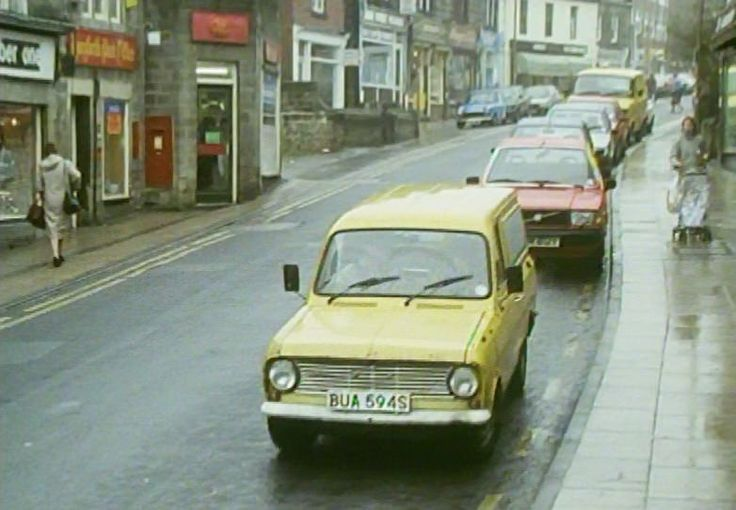 https://flic.kr/p/J7hnhr | Horsforth | Another screenshot from The 1987 comedy-drama The Beiderbecke Tapes. Trevor Chaplain (James Bolam) drove a battered Bedford HA van, seen here in Town Street, Hosrforth, in Leeds. The Post Office in the background was part of the scene and has since relocated across the road, although the old post box and stamp machines remain, painted black, the building now being a beauty parlour. The 1978 van was on the road until 1990.